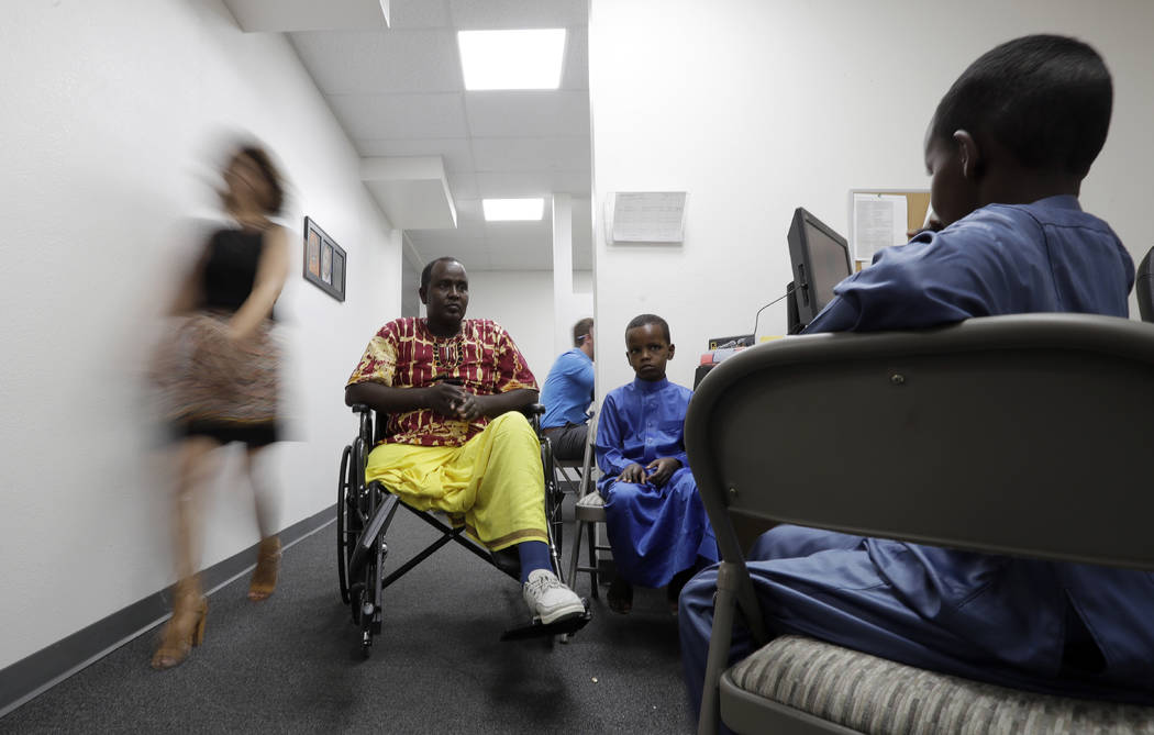 Ali Said, of Somalia, center, waits at a center for refugees with his two sons in San Diego on July 6. Said, whose leg was blown off by a grenade, says he feels unbelievably lucky to be among one  ...