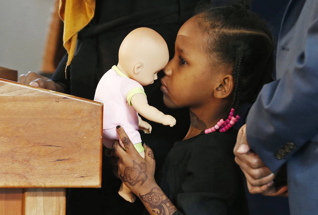 FILE - In this Feb. 3, 2017, file photo, four-year-old Somali refugee Mushkaad Abdi holds her doll as her mother, Samira Dahir, talks during a Minneapolis news conference one day after she was reu ...
