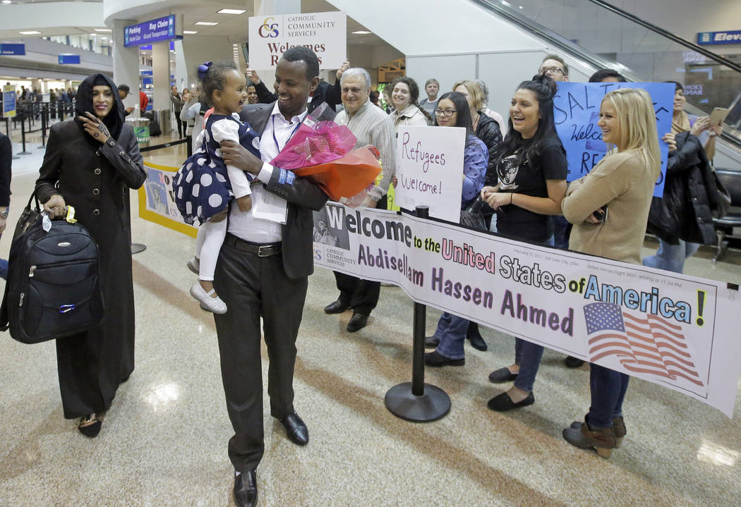 Abdisellam Hassen Ahmed, a Somali refugee who had been stuck in limbo after President Donald Trump temporarily banned refugee entries, walks with his wife Nimo Hashi, and his 2-year-old daughter,  ...