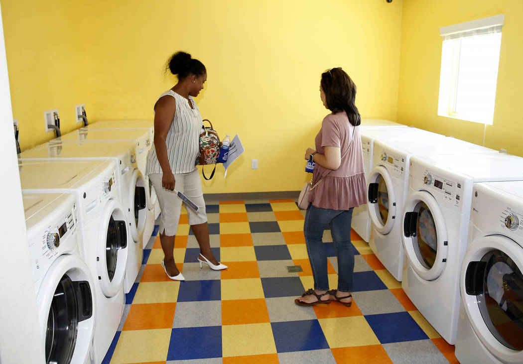 Yolanda Scott, left, and Shalimar Cabrera tour the laundry room at the new Shannon West Homeless Youth Center during the grand opening ceremony of the center on 1650 E. Flamingo Road, on Friday, J ...