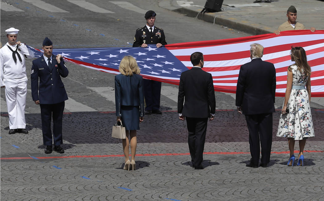 French President Emmanuel Macron, third right,, and his wife Brigitte, fourth left, with U.S President Donald Trump and First Lady Melania Trump stand in front of a huge American flag after the Ba ...