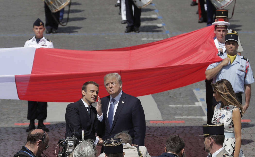 French President Emmanuel Macron talks with U.S President Donald Trump next to a huge French flag after the Bastille Day parade in Paris on Friday. (AP Photo/Markus Schreiber)