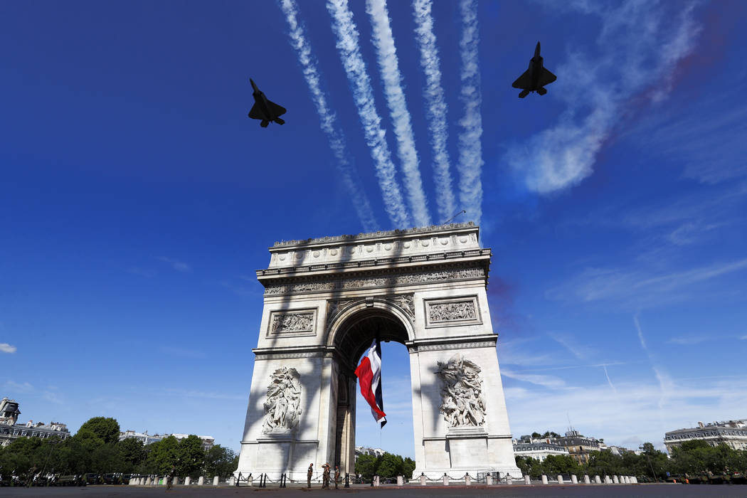 French war planes fly over the Arc de Triomphe in Paris on Friday. Paris tightened security before its annual Bastille Day parade, which this year is being opened by American troops with President ...