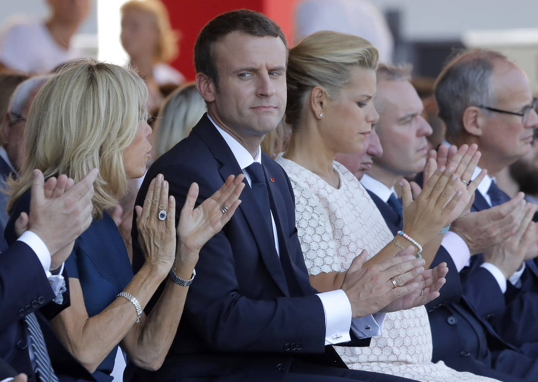 French President Emmanuel Macron looks at his wife Brigitte, left, during a ceremony in Nice, southern France on Friday. Macron has arrived in the Riviera city of Nice for commemorations one year  ...