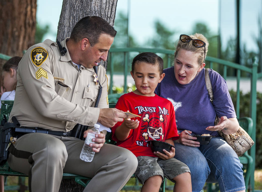 "Sgt. Steve Armbruster gives a patch to Aidan Ramos, 5, while his mother Catherine watches during a ""Chill with a Cop"" event hosted by Metropolitan Police Downtown Area Command at the Anderson Dair ..."