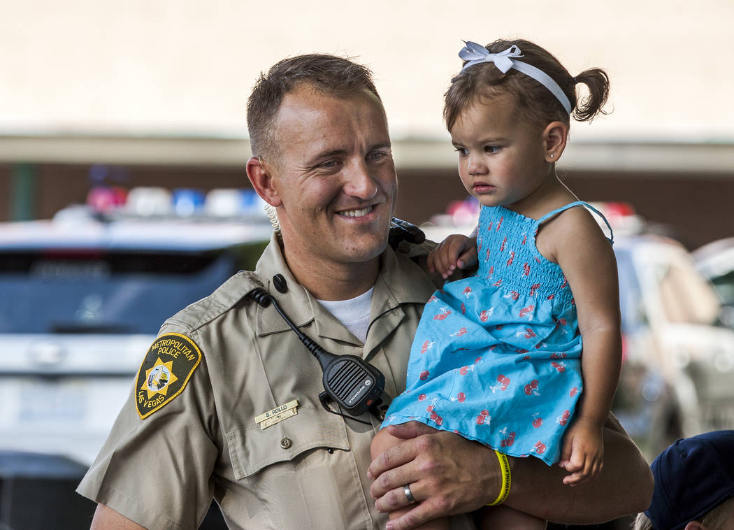 "Officer Shad Rollo holds his daughter Ivy, 2, during a ""Chill with a Cop"" event hosted by Metropolitan Police Downtown Area Command at the Anderson Dairy in Las Vegas on Tuesday, July 18, 2017. (P ..."