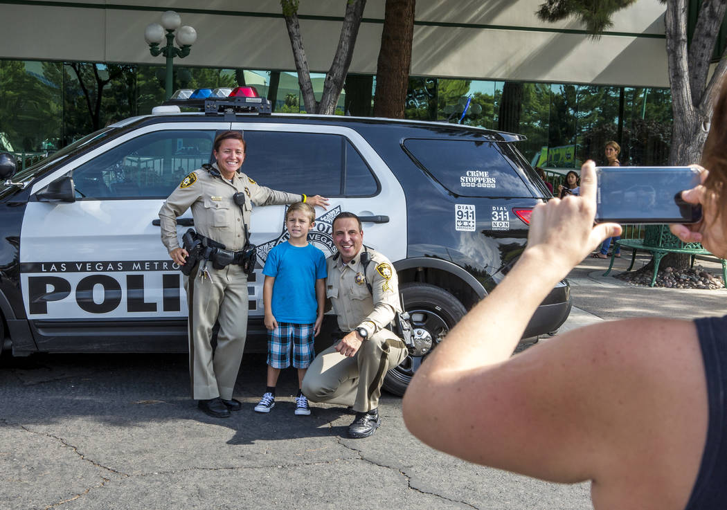 "Savanah Funicello takes a photo of her son Gabriel, 5, with Officer Phalon Mauntel, left, and Sgt. Steve Armbruster during a ""Chill with a Cop"" event hosted by Metropolitan Police Downtown Area Co ..."
