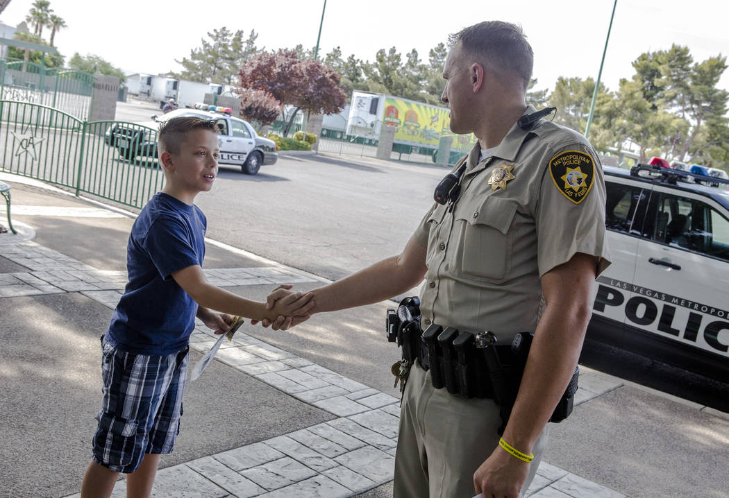 "Officer Shad Rollo shakes hands with Jacob Rieger, 11, during a ""Chill with a Cop"" event hosted by Metropolitan Police Downtown Area Command at the Anderson Dairy in Las Vegas on Tuesday, July 18, ..."