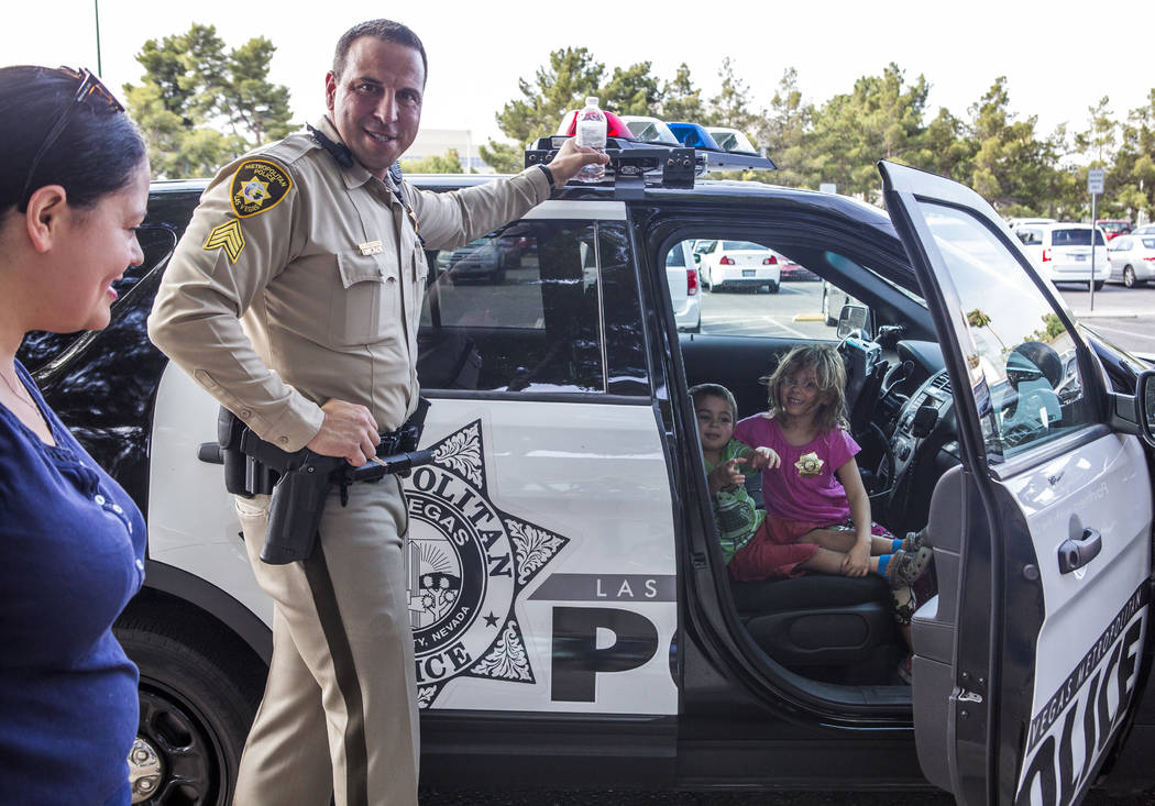 "Paisley Gupton, 5, right, and her sister Bennett , 3, get a chance to sit in a police cruiser as their mother Natalie Gupton and Sgt. Steve Armbruster look on during a ""Chill with a Cop"" event hos ..."