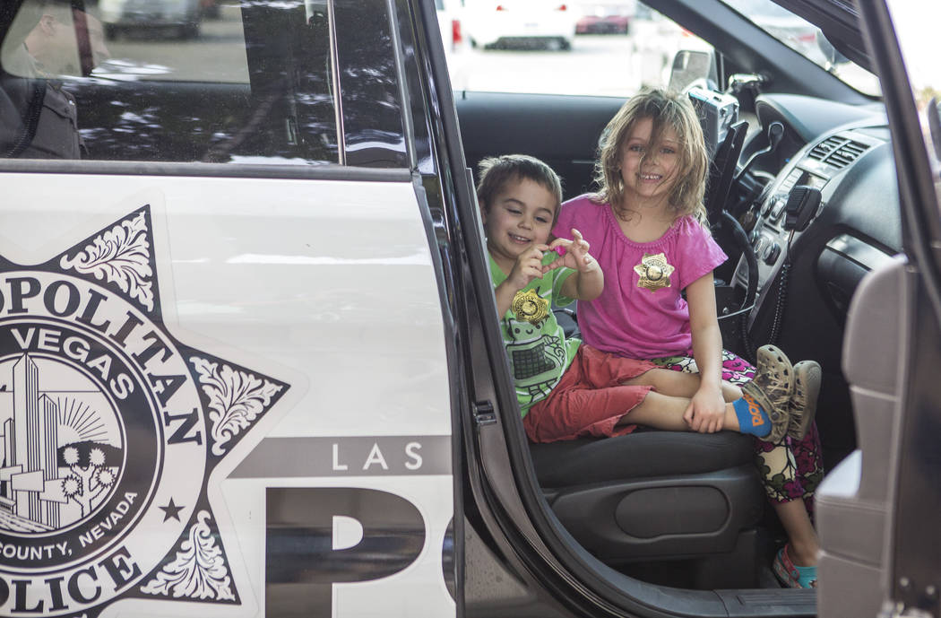 "Paisley Gupton, 5, right, and her sister Bennett , 3,  get a chance to sit in a police cruiser during a ""Chill with a Cop"" event hosted by Metropolitan Police Downtown Area Command at the Anderson ..."