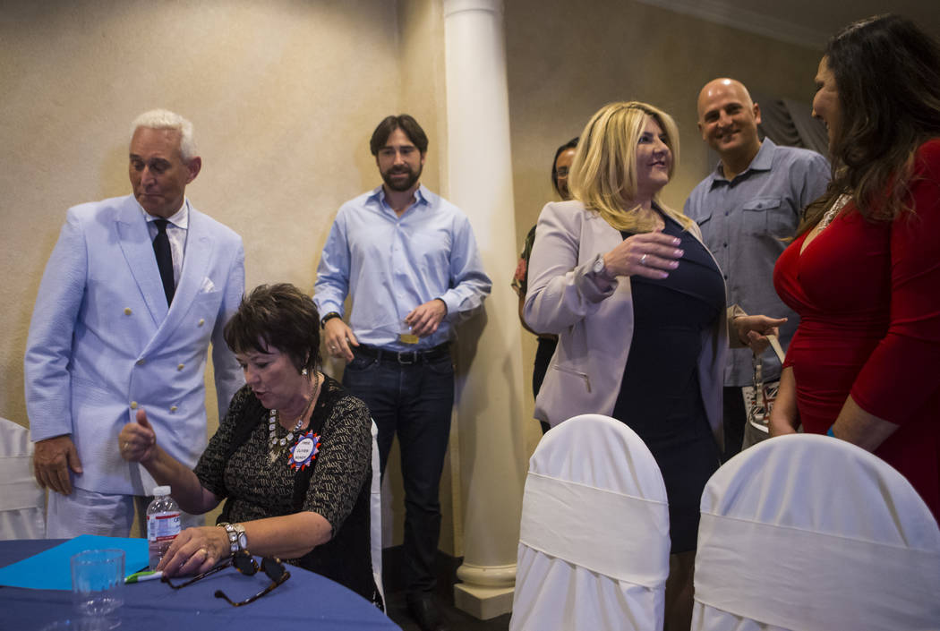Political consultant Roger Stone, left, talks with Carol Bundy, second from left, as Las Vegas City Councilwoman Michele Fiore, fourth from left, greets people at a fundraising event in support of ...