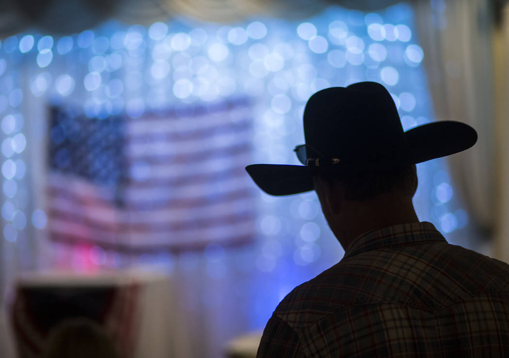 An attendee wearing a cowboy hat is silhouetted at a fundraising event in support of the Bundy family at Rainbow Gardens in Las Vegas on Saturday, July 15, 2017. Chase Stevens Las Vegas Review-Jou ...