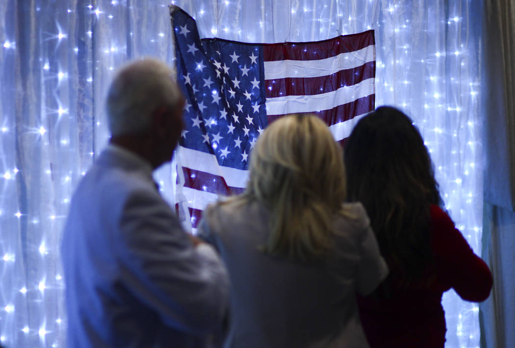 Political consultant Roger Stone, left, and Las Vegas City Councilwoman Michele Fiore, second from left, stand for the pledge of allegiance at a fundraising event in support of the Bundy family at ...