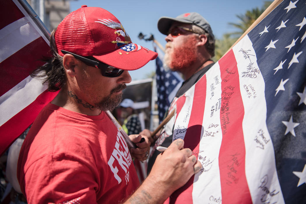 Lanahan Russell, Virginia resident, signs a flag at a rally to support defendants in the Bundy standoff case at the Lloyd George U.S. Courthouse on Saturday, July 15, 2017, in Las Vegas. Morgan Li ...