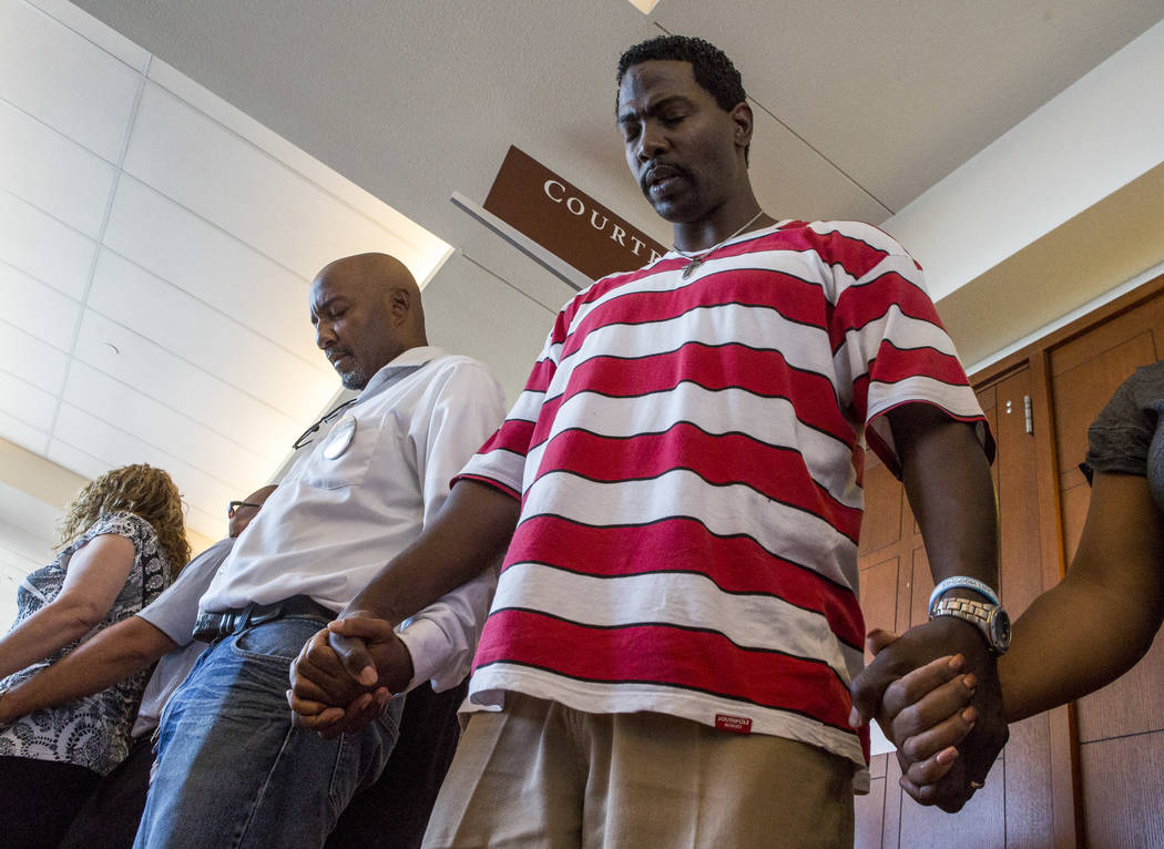 Seaboron Dickson, center right, joins others in praying for justice for Roland Pleasant before sentencing for Eric Javon Bell at the Regional Justice Center in Las Vegas on Monday, July 17, 2017.  ...