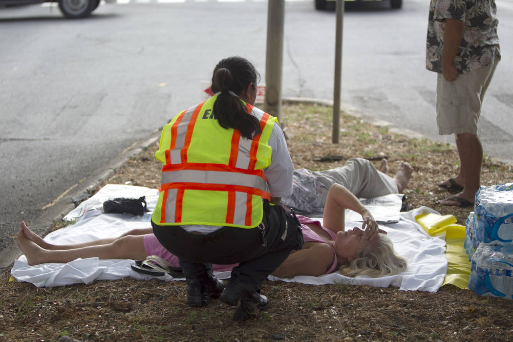 A paramedic checks on a woman, lying on a median, after she and others exited the Marco Polo apartment complex as firefighters continue to battle a blaze at the high-rise, Friday, July 14, 2017, i ...