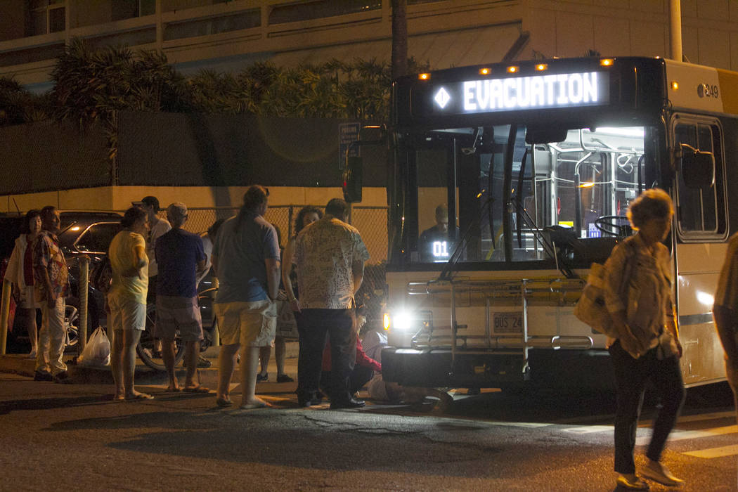 An evacuation bus takes residents of the Marco Polo building to a nearby shelter after a deadly fire at the building, Friday, July 14, 2017, in Honolulu. (Marco Garcia/AP)