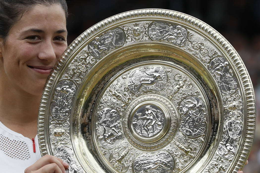 Spain's Garbine Muguruza holds the trophy after defeating Venus Williams of the United States in the Women's Singles final match on day twelve at the Wimbledon Tennis Championships in London Satur ...