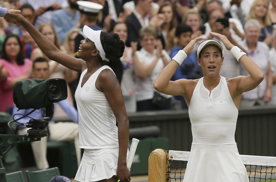 Spain's Garbine Muguruza, right, celebrates after beating Venus Williams of the United States to win the Women's Singles final match on day twelve at the Wimbledon Tennis Championships in London S ...