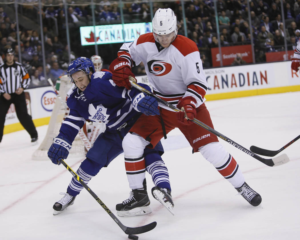 Feb 25, 2016; Toronto, Ontario, CAN; Toronto Maple Leafs forward Brendan Leipsic (49) battles with Carolina Hurricanes defenseman Noah Hanifin (5) for the puck during the second period at the Air  ...