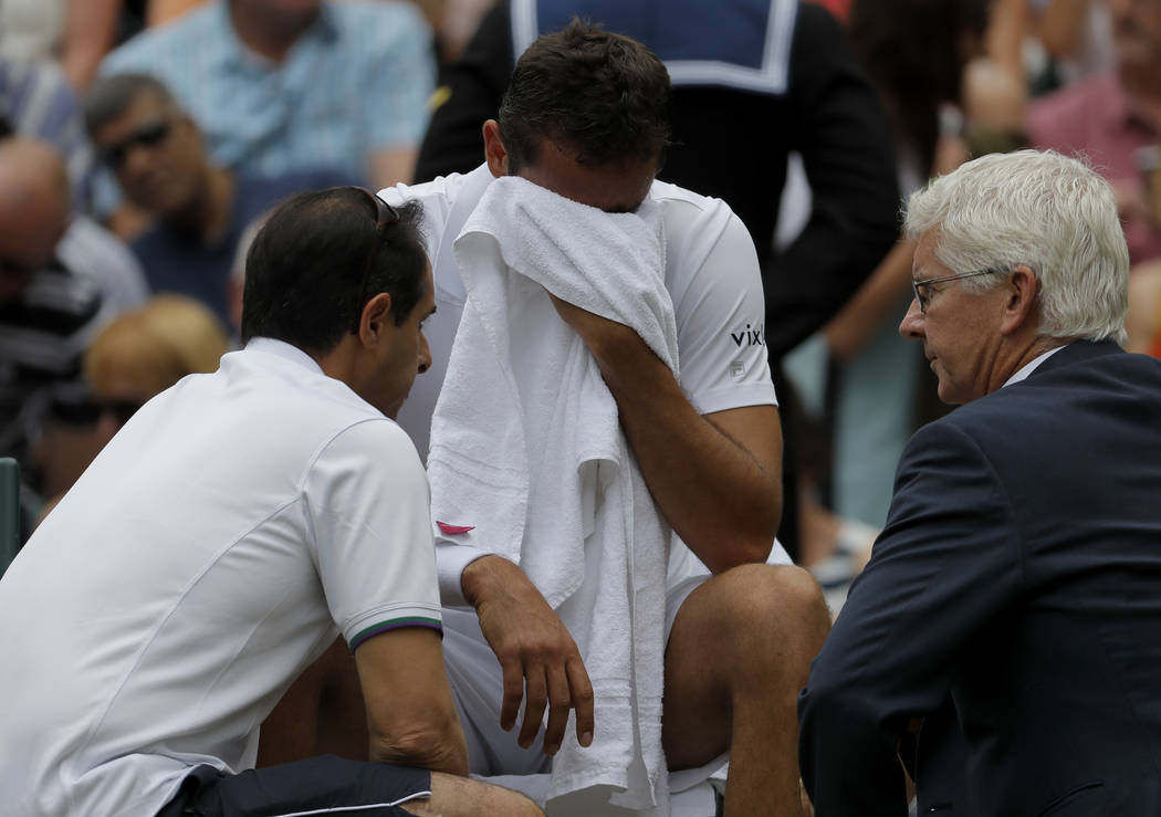 Croatia's Marin Cilic receives treatment during a change of ends break as he plays Switzerland's Roger Federer in the Men's Singles final match on day thirteen at the Wimbledon Tennis Championship ...