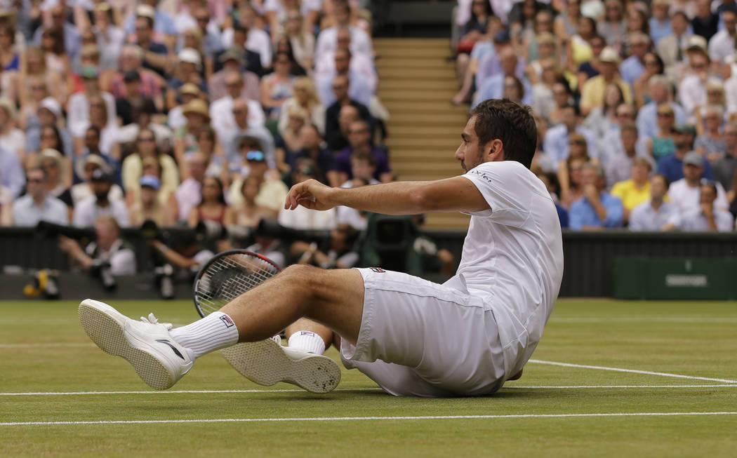Croatia's Marin Cilic takes a tumble after returning to Switzerland's Roger Federer in the Men's Singles final match on day thirteen at the Wimbledon Tennis Championships in London Sunday, July 16 ...