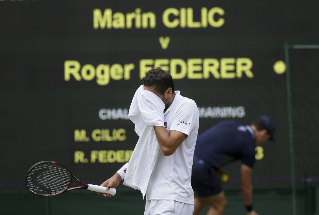 Croatia's Marin Cilic walks back to his seat after his service was broken by Switzerland's Roger Federer in the Men's Singles final match on day thirteen at the Wimbledon Tennis Championships in L ...