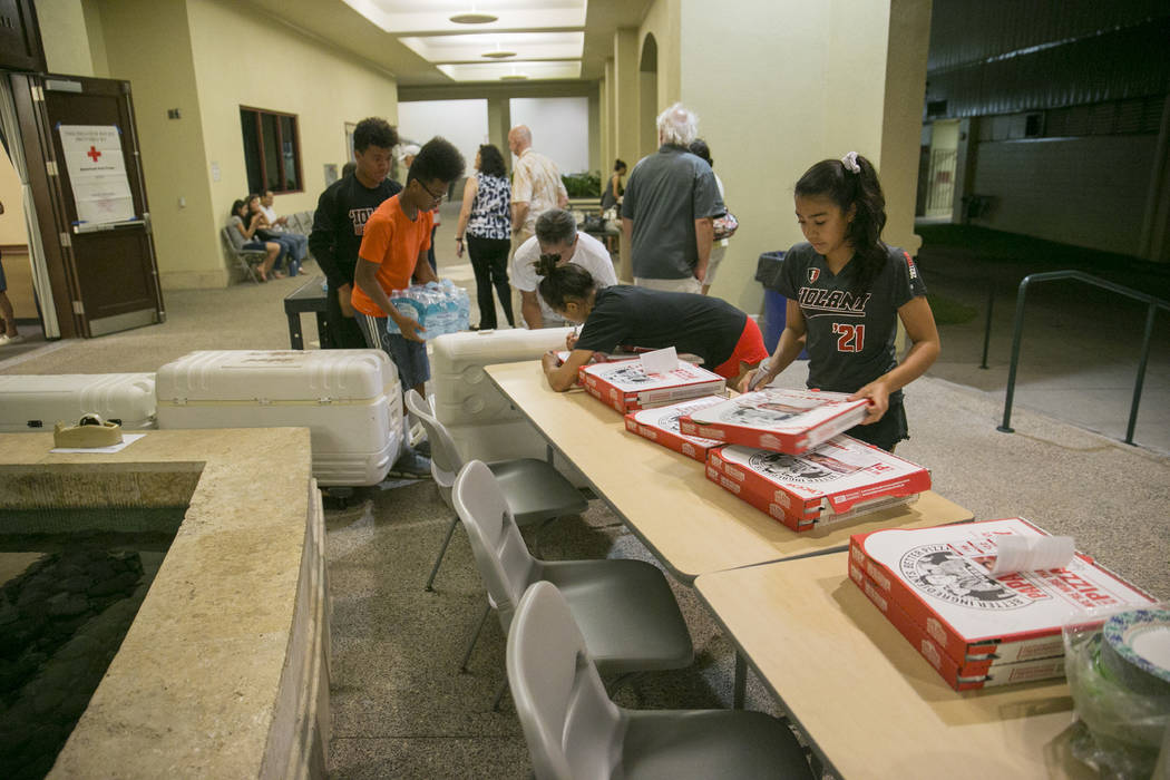 Volunteers prepare food and drinks at a school for the residents of the Marco Polo building, Friday, July 14, 2017, in Honolulu. A deadly fire broke out in the building killing three people and se ...