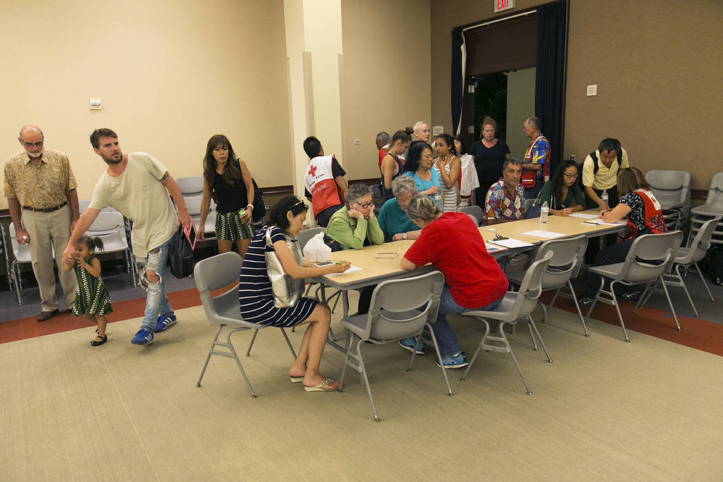 Residents of the Marco Polo building register at a shelter for overnight accommodations after a deadly fire tore through the high rise building, Friday, July 14, 2017, in Honolulu. (Marco Garcia/AP)