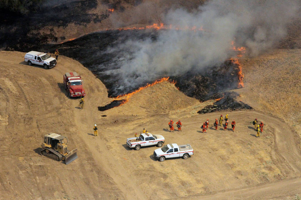 Firefighting crews from the California Department of Forestry and Fire Protection (CAL FIRE) move into position to fight the Garza fire as California Army National Guard helicopters fly overhead a ...