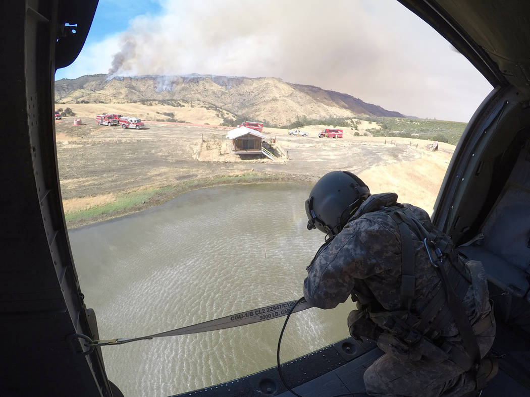 Staff Sergeant Ge Xiong, crew chief aboard a California Army National Guard UH-60 Black Hawk helicopter, watches a 2,600-gallon Bambi Bucket submerge into a pond July 13,2017, during the Garza fir ...