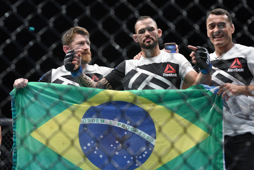 Santiago Ponzinibbio (blue gloves) poses with his corner crew after defeating Gunnar Nelson (not pictured) during UFC Fight Night at SSE Hydro. (Per Haljestam-USA TODAY Sports)