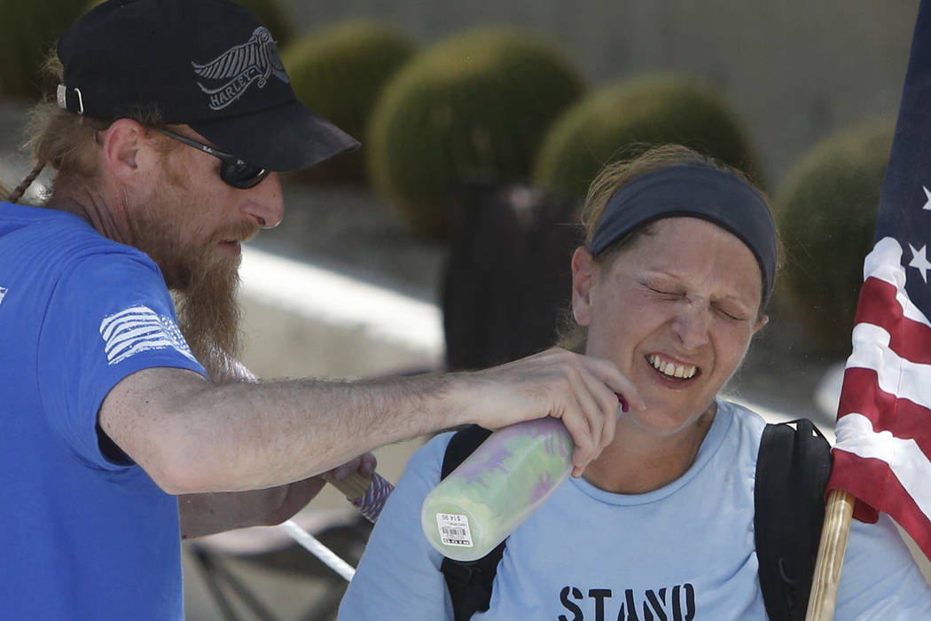 Ty Young uses water spray bottle to cool down a woman, who declined to give her name, outside the Lloyd George U.S. Court house on Monday, July 17, 2017, in Las Vegas. (Bizuayehu Tesfaye/Las Vegas ...