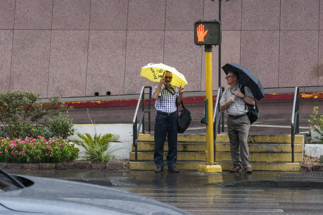 Pedestrians wait to cross Flamingo Road near Bally's while protecting themselves from the rain during a storm in Las Vegas on Monday, July 17, 2017.  Patrick Connolly Las Vegas Review-Journal @PCo ...