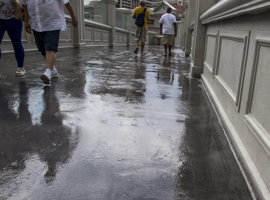 Pedestrians cross a wet Las Vegas Boulevard near Caesars Palace after a rainstorm on the Las Vegas Strip on Monday, July 17, 2017.  Patrick Connolly Las Vegas Review-Journal @PConnPie