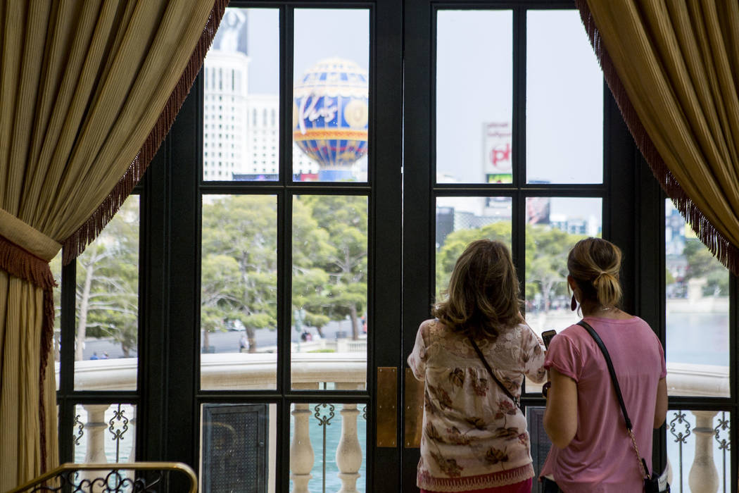 Bellagio visitors look out at dark clouds during a rainstorm on the Las Vegas Strip on Monday, July 17, 2017.  Patrick Connolly Las Vegas Review-Journal @PConnPie