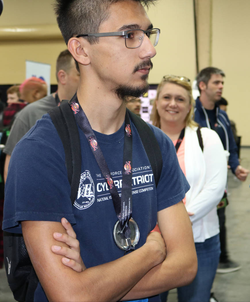"Chance Chhet, 17, waits in line to play the latest version of a video game called ""Marvel vs. Capcom: Infinite"" while his family, including his mom Renae Bonestroo, waits for him at the 2017 Evolu ..."