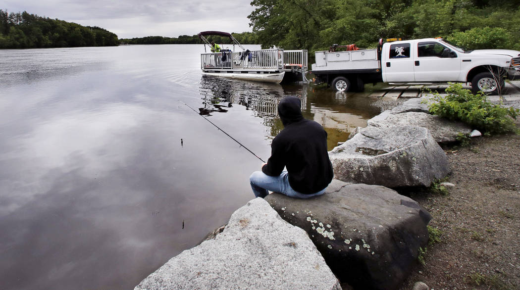 """In this Wednesday June 7, 2017 photo, Kevin Garcia fishes along the banks of the Merrimack River as a """"Clean River Project"""" recovery boat is offloaded in Chelmsford, Mass. Syring ..."""