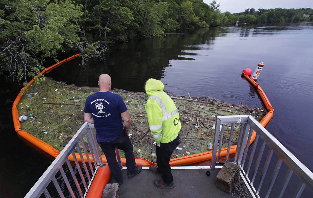 """In this Wednesday, June 7, 2017 photo, activist Rocky Morrison, left, and volunteer Dalton Abbott, of the """"Clean River Project"""" examine a boom filled with waste collected from a  ..."""