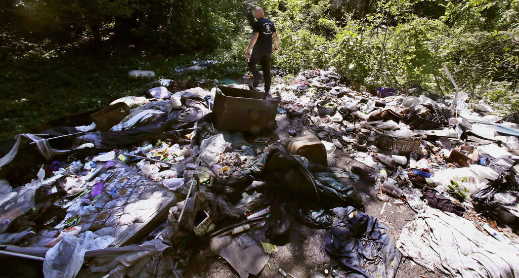 In this Wednesday June 7, 2017 photo, activist Rocky Morrison walks through an encampment where opioid addicts shoot up along the Merrimack River in Lowell, Mass. Morrison leads a cleanup effort a ...