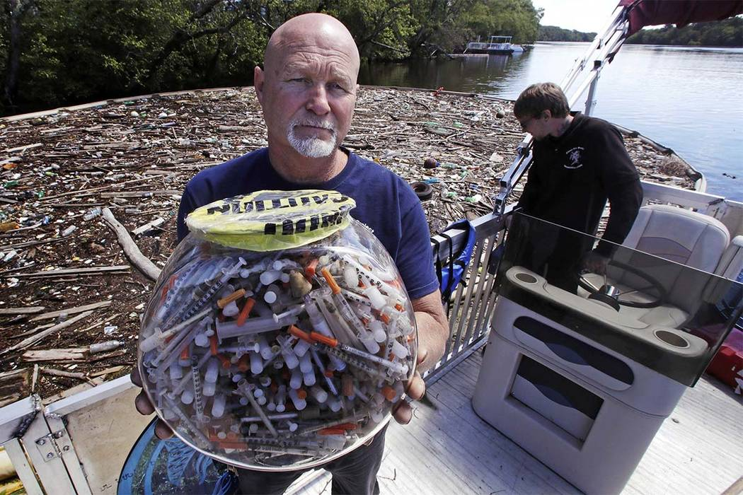 """In this Wednesday June 7, 2017 photo, activist Rocky Morrison, of the """"Clean River Project"""", holds up a fish bowl filled with hypodermic needles, that were recovered during 2016, ..."""