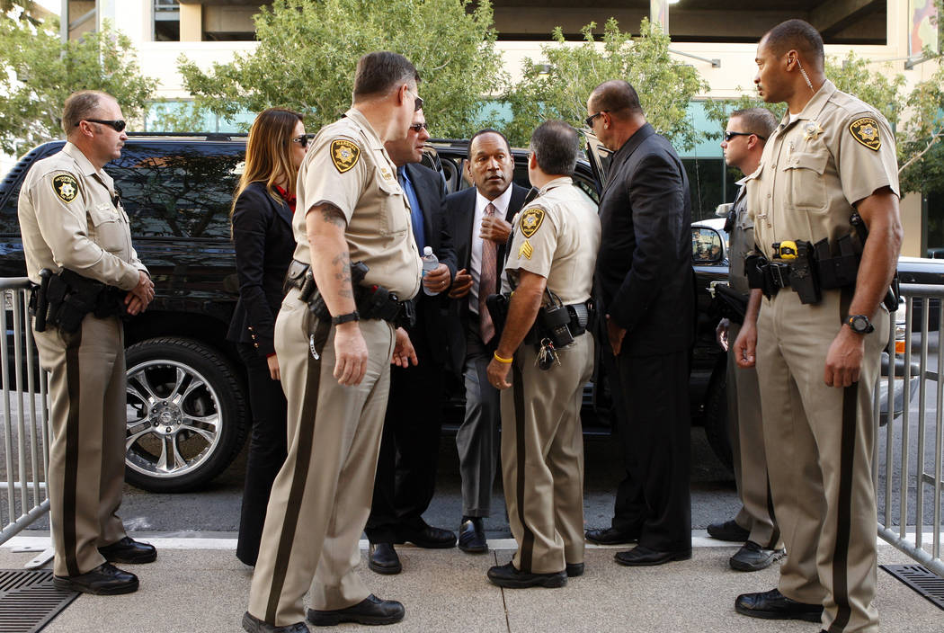 FILE - In this Sept. 9, 2008 file photo, O.J. Simpson, center, arrives at the Clark County Regional Justice Center on the second day of jury selection for his trial in Las Vegas. (AP Photo/John Lo ...
