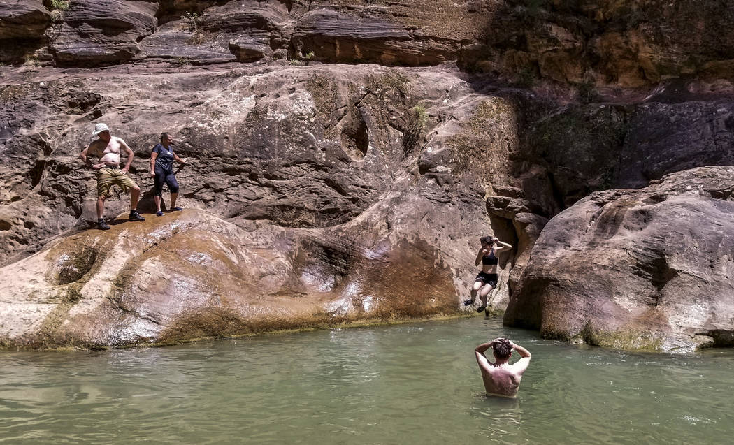 Zion National Park visitors jump off rocks along The Narrows, a river hike through the Virgin River, at Zion National Park in Utah on Friday, July 14, 2017. (Patrick Connolly/Las Vegas Review-Jour ...