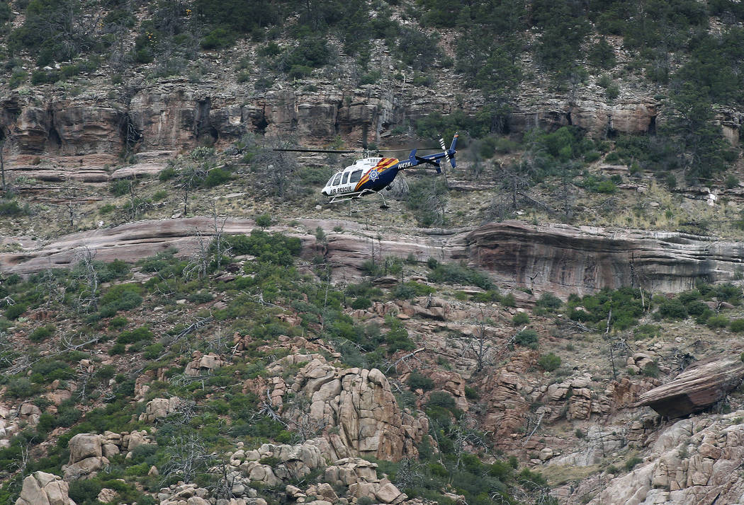 A helicopter flies above the rugged terrain along the banks of the East Verde River during a search and rescue operation for victims of a flash flood on Sunday, July 16, 2017, in Payson, Ariz. Sea ...