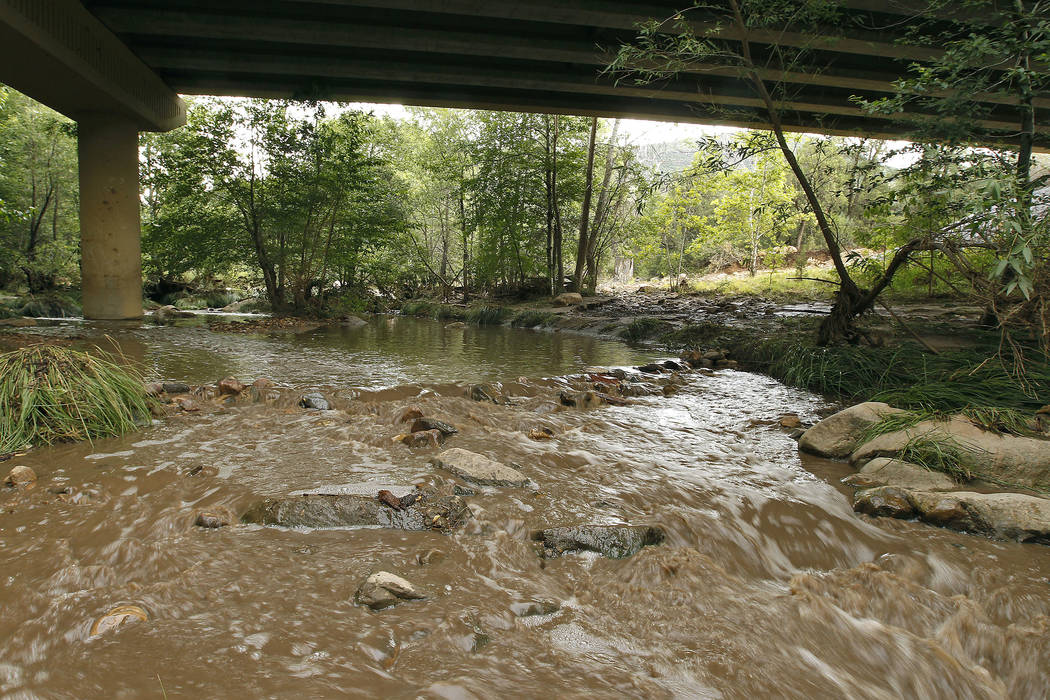 Muddy floodwaters of the East Verde River flow under a bridge where one victim of the flash flood was found during a search and rescue operation by the Gila County Sheriff's Office on Sunday, July ...