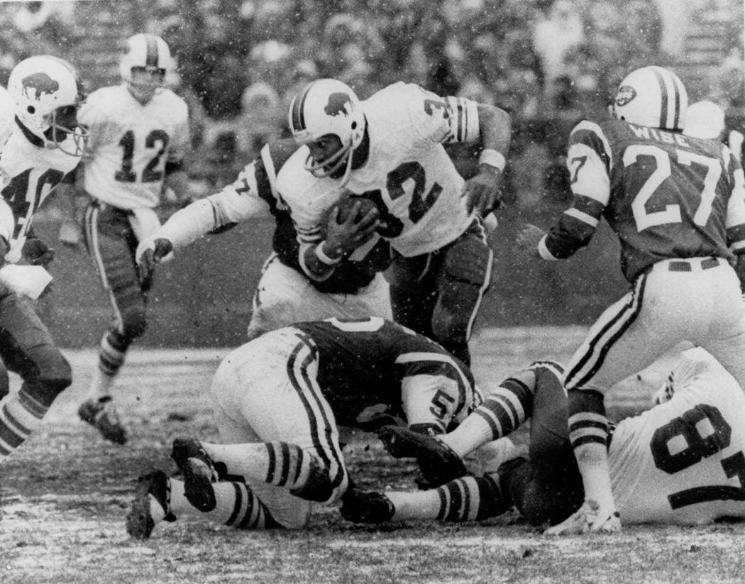 FILE - In this Dec. 16, 1973 file photo, Buffalo Bills' O.J. Simpson (32) runs against the New York Jets in the first quarter of an NFL football game at Shea Stadium in New York. Also shown are th ...