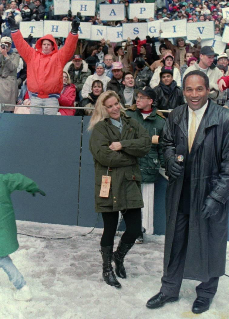 FILE - In this Nov 25, 1993 file photo, O.J. Simpson stands with his wife Nicole Brown Simpson while broadcasting on the sidelines during the Thanksgiving Day NFL football game between the Dallas  ...