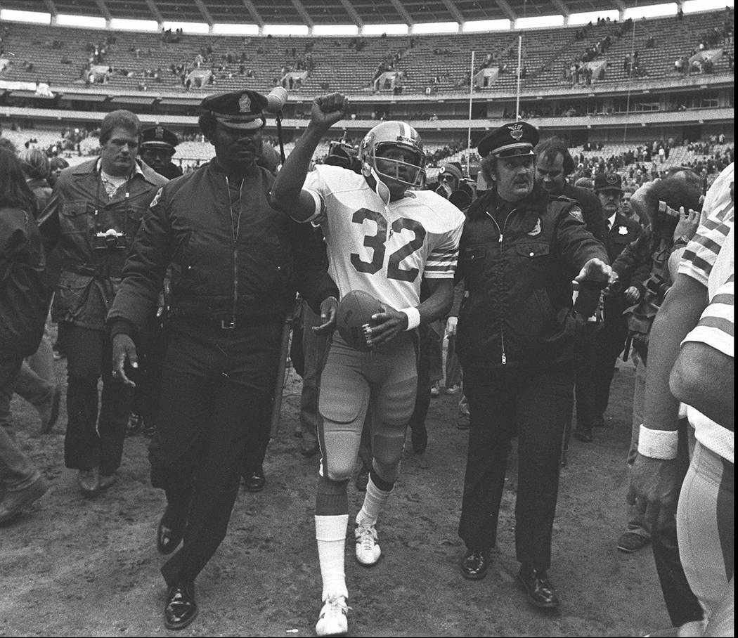 FILE - In this Dec. 16, 1979 file photo, San Francisco 49ers running back O.J. Simpson is escorted from the field by police after the final NFL football game of his career against in the Atlanta F ...