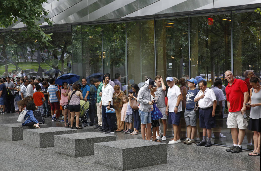 In this July 11, 2017 photo, visitors to the National September 11 Memorial and Museum take shelter beneath a museum overhang during a sudden rainstorm in New York. Last winter the U.S. tourism in ...