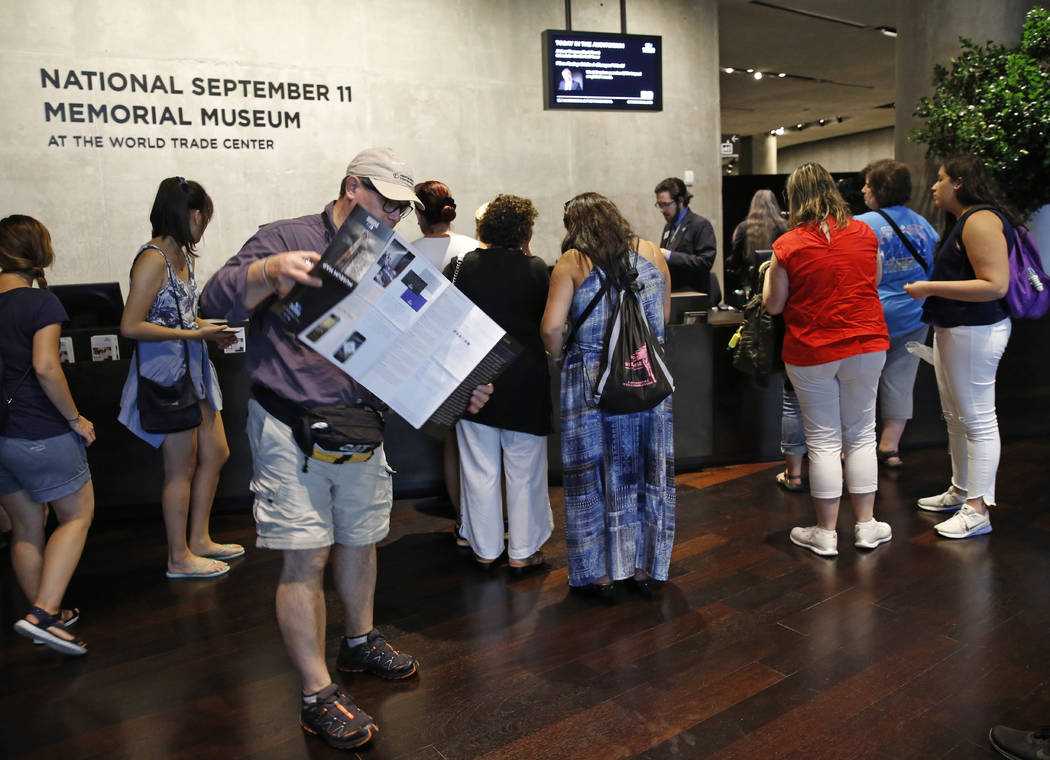 """In this July 11, 2017 photo, visitors to the National September 11 Memorial and Museum pick up maps and guides in New York. Last winter the U.S. tourism industry worried about a """"Trump slump,"""" fea ..."""